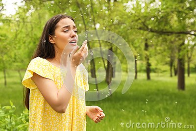 Young woman suffering from seasonal allergy outdoors