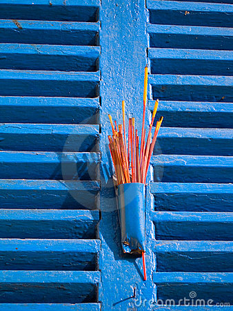 Red Incense on Blue Window Shutters