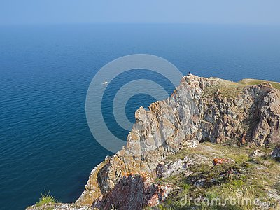 Tourist on the top of the cliff of Olkhon Island. View of Lake Baikal