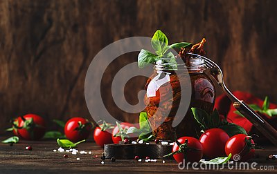 Dried tomatoes in olive oil with green basil and spices in glass jar on wooden kitchen table, rustic style, place for text