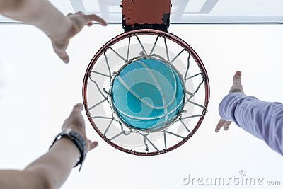 stock image of reaching for a basketball in the net