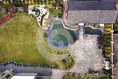 Aerial view of beautifully landscaped property complex. Roofs of recreation house cottage, pond in ecological area on bright sunny