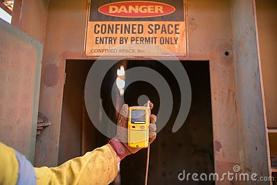 Worker hand holding gas test detector device while commencing safety gas testing atmosphere at main entry and exit on confined spa
