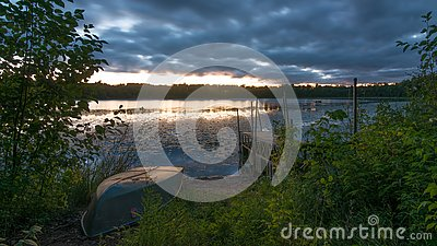 Sunset with old dock and old row boat on small remote lake in Northern Wisconsin - clouds and weather coming in