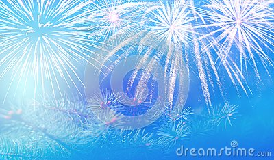 Christmas pine branch on a beautiful blue background with sparks and fireworks splashes, wonderful New Year`s mood.