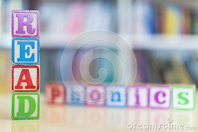 Alphabet blocks spelling the words read and phonics in front of a bookshelf
