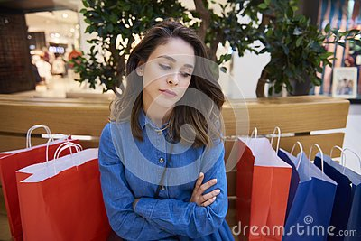 Sad woman spent all her money during big shopping