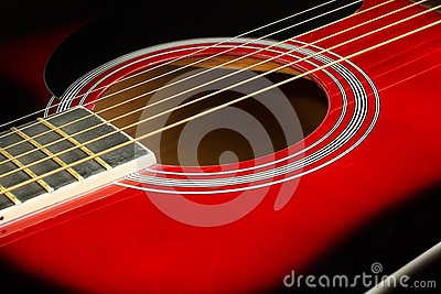 stock image of closeup of a six stringed red acoustic guitar. music entertainment background