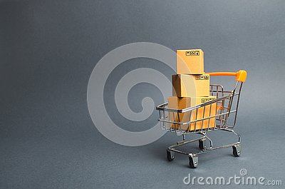 A pile of cardboard boxes in a supermarket trolley. concept of shopping in the online store . E-commerce, sales and sale of goods