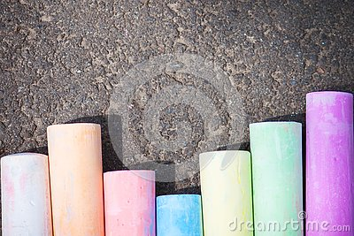 Colored chalk on asphalt. Children`s creativity games. Background with place for text, frame, flat lay, copy space. Back to schoo