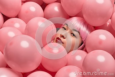 Attractive lady in pink wig lying under balloons