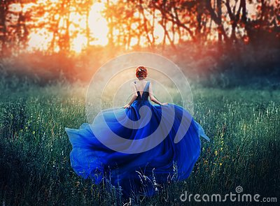 Princess, with a elegant hairstyle, runs through a forest meadow to meet a fiery sunset with a haze. A luxurious blue