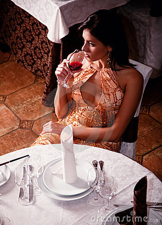 Beautiful girl tastes the wine at a restaurant