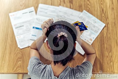 Very stressed young sitting Asian woman hands holding the head worry about find money to pay credit card debt.