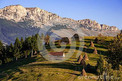 Landscape from Romania with haystack and old wooden house in the mountain of Transylvania