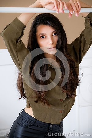 Photogenic, confident, young model or brunette girl with her hair down, with her hands up, looking at the camera with a calm look
