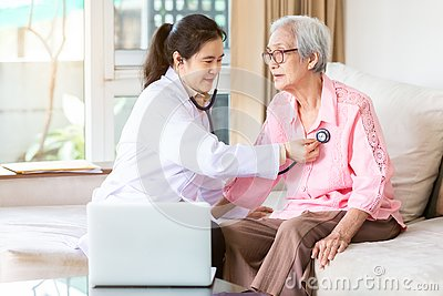 Family doctor or nurse checking smiling senior patient using stethoscope during home visit,young female home caregiver,health