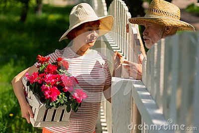Neighbors standing near fence talking about planting flowers