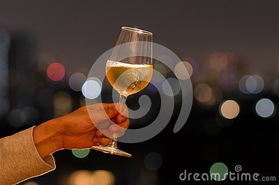 Hand holding a glass of white wine toasting to celebration and party concept on rooftop bar with colorful bokeh of city light and
