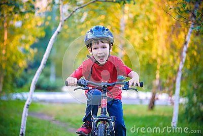 Happy kid boy of 6 years having fun in autumn forest with a bicycle on beautiful fall day. Active child making sports. Safety,