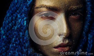 Pure gold. Vogue concept. Golden skin. Attractive woman pretty face with makeup and body art metallized color. Spa and