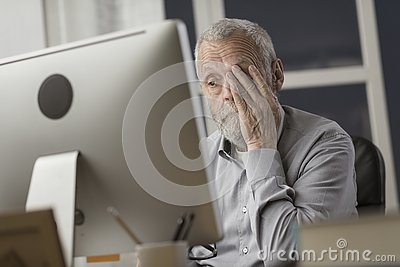 Confused senior citizen using a computer