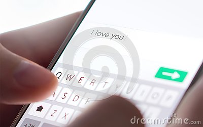 Sending I love you text message with mobile phone. Online dating, texting or catfishing concept. Romance fraud, scam.