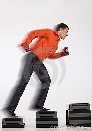 Businessman running up with dumbbells