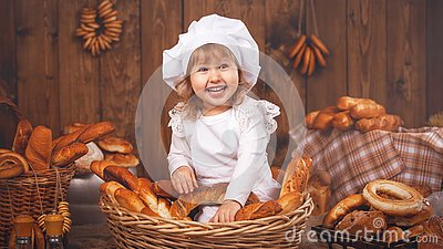 Happy baby chef in wicker basket laughing playing chef in bakery, lots of bread baking.