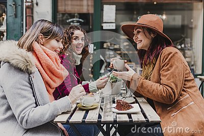 Three women friends having coffee in a terrace in Oporto, Portugal. Having a fun conversation. Lifestyle, tourism and holidays