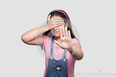 I don`t want to look at this. Portrait of scared or shy girl in pink t-shirt and blue denim overalls standing, covering her eyes