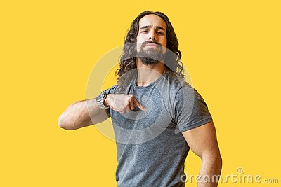 Portrait of proud bearded young man with long curly hair in grey tshirt standing, pointing himself and looking at camera with