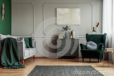 Abstract painting on grey wall o contemporary living room interior with emerald green armchair with round pillow, commode and