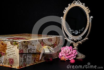 Vintage Oval Desk Mirror with white frame, Potpourri pieces and a keepsake box on black background