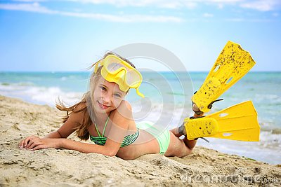 Girl sunbathing in mask and fins for scuba diving