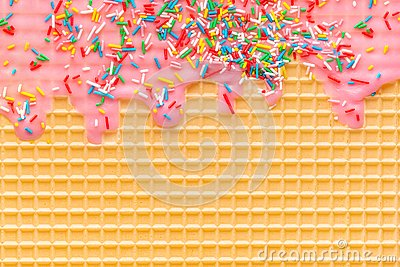 Golden waffle texture with pink icing and sprinkles, background for your design