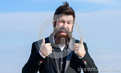 Hopeful and confident about future. Thumbs up gesture. Man bearded optimistic businessman wear formal suit sky