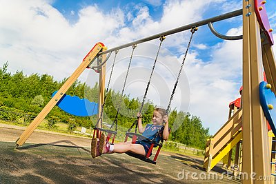 Child playing on outdoor playground in rain. Kids play on school or kindergarten yard. Active kid on colorful swing. Healthy