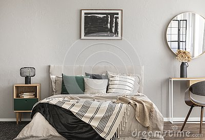 Abstract black oil painting in frame on empty beige wall of cozy bedroom