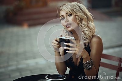 Portrait of gorgeous elegant blond woman sitting at the table in the nice street cafe holding a cup with frothy latte