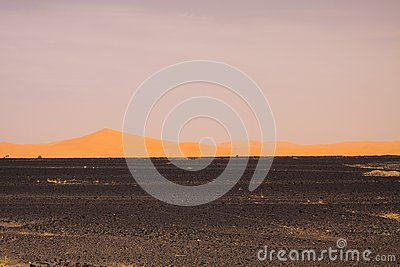View over endless burned black flat waste stony land on golden sand dunes and blurred gloomy sky, Erg Chebbi, Morocco