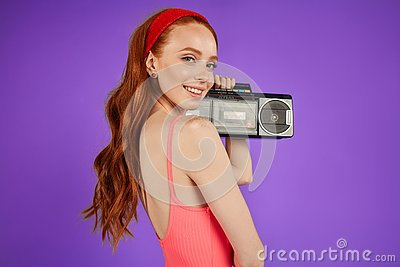 Red-haired girl with freckles stands with portable audio player, looks playfully in camera