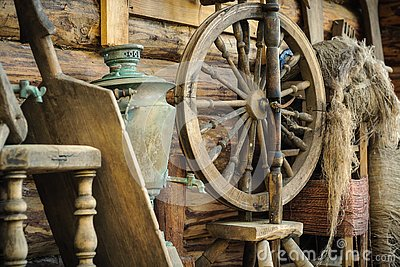 antique wooden spinning wheel with accessories and old household items against a rough wooden log wall