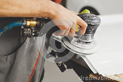 Sanding of uneven elements of the car after painting and varnishing. Vehicle repair in service station.