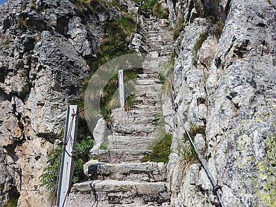 Steep stairway carved out of stone on a mountain path. Steel cables on its sides. Orobie. Italian Alps