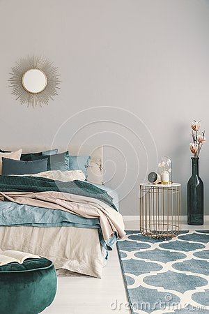 Flowers in stylish bottle like vase next to trendy nightstand with clock in beautiful bedroom interior with beige and emerald