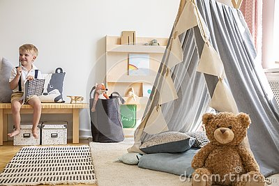 Smiling kid sitting on bench with notebook, real photo of natural playroom interior with scandinavian tent and teddy bear