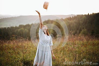 Stylish carefree boho girl throwing her hat in the sky in sunny light  at atmospheric sunset. Happy hipster woman in linen rustic