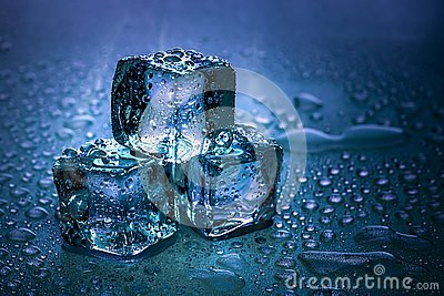 Ice cubes and water melt on cool background. Ice blocks with cold drinks or beverage