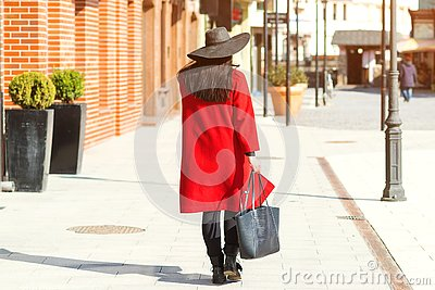 Stylish beautiful woman walking in street. Girl wearing red coat, black hat and holding trendy bag. Fashion outfit, autumn trend,